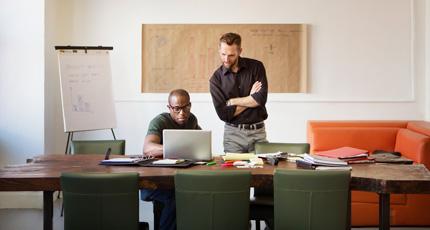 Frontansicht zweier Männer, die an einem Tisch in einem Konferenzraum arbeiten und auf einen geöffneten Laptop schauen.