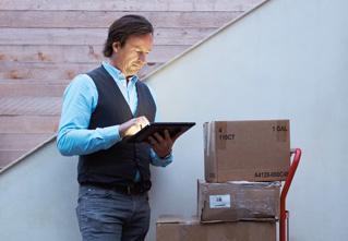 Ein Mann sitzt neben einem Kartonstapel und arbeitet mit Office Professional Plus 2013 auf einem Tablet.