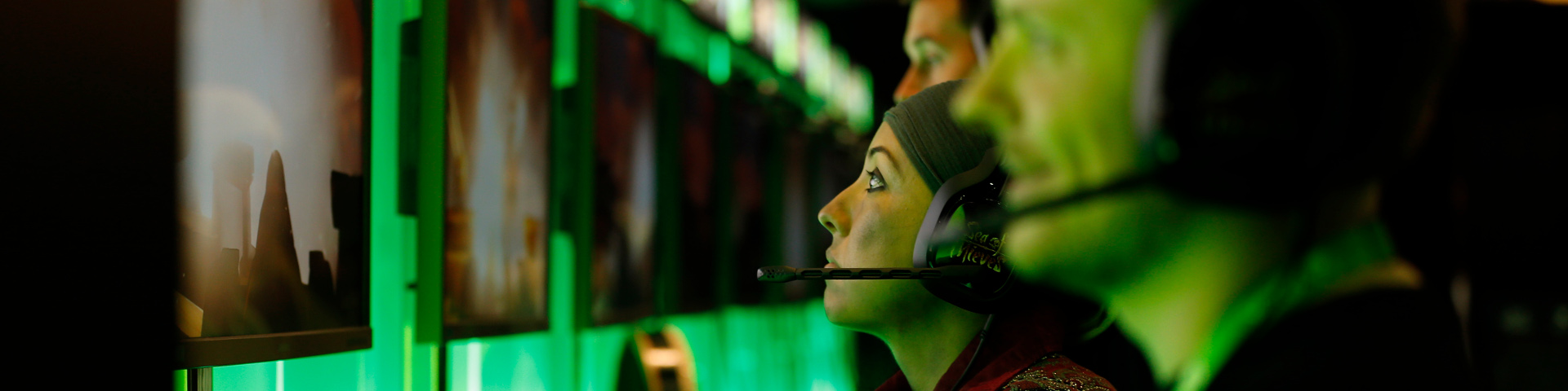 Xbox-Spieler sitzen mit Kopfhörern vor PCs und spielen Games