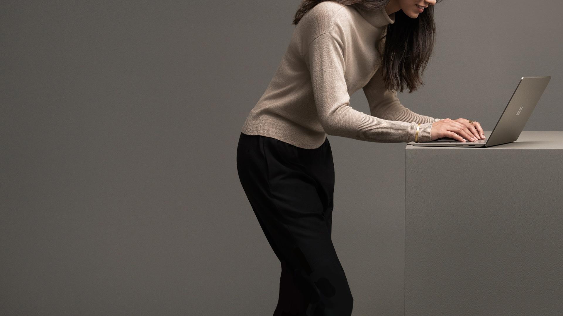 Frau, die auf der Tastatur ihres Surface Laptops in Graphit und Gold tippt.