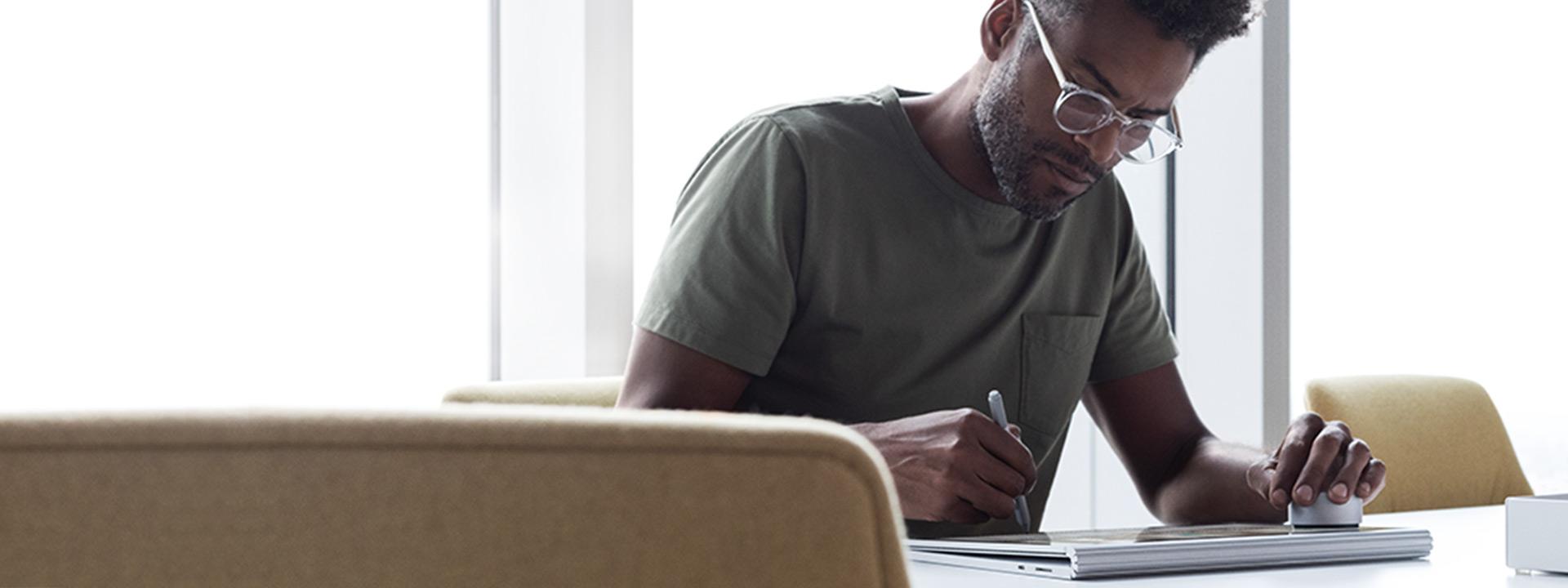 Ein Mann sitzt an einem Tisch und verwendet sein Surface-Gerät und Zubehör.