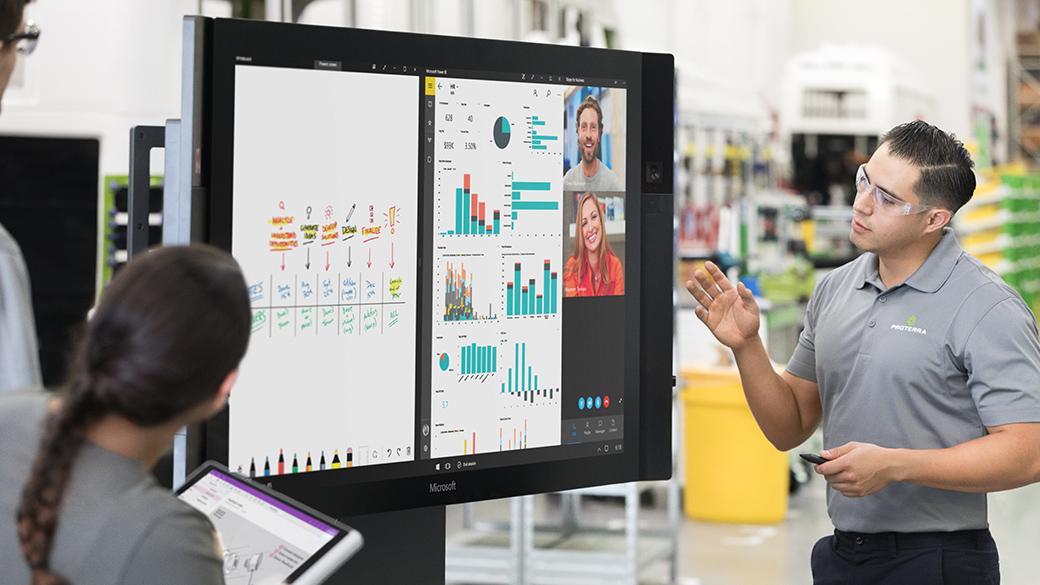 Ein Mann und eine Frau blicken auf einen Bildschirm auf einem Surface Hub, der das Whiteboard, Power BI und Skype for Business enthält.