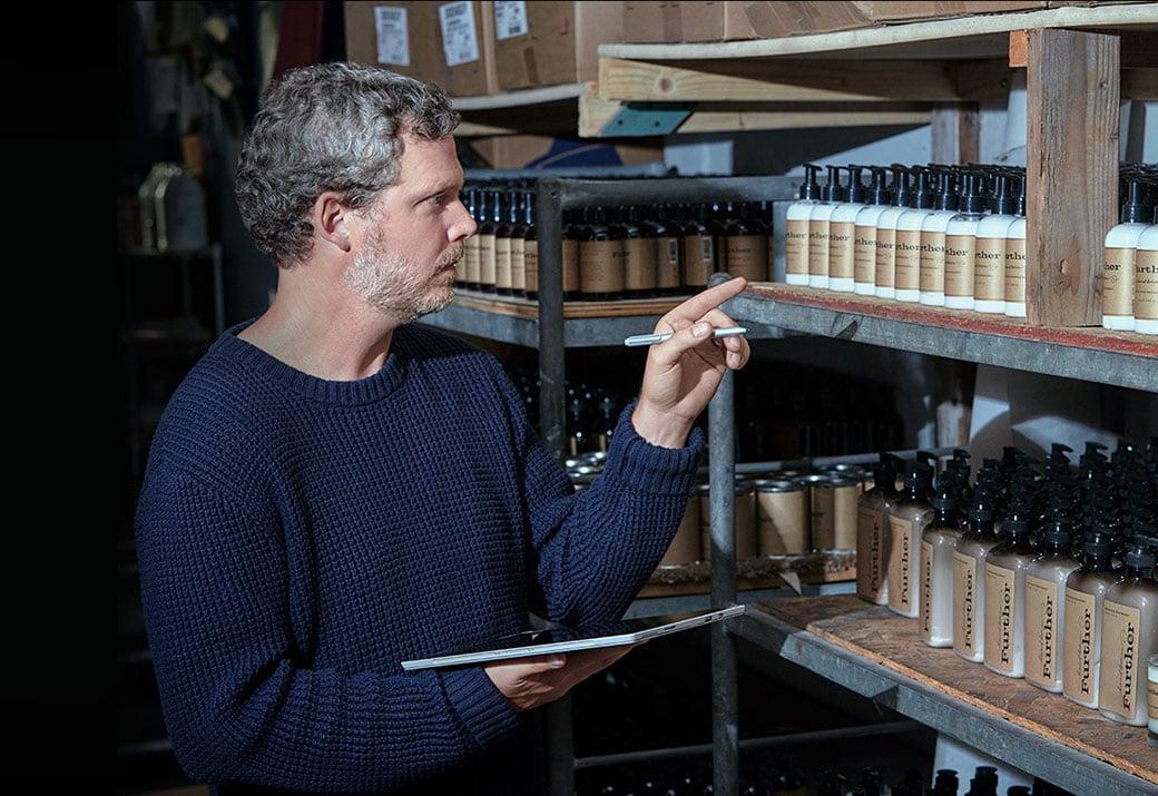 Bild eines Mannes bei der Inventur von Seifen und Lotionen mit Surface Pro4 und Stift im Tablet-Modus