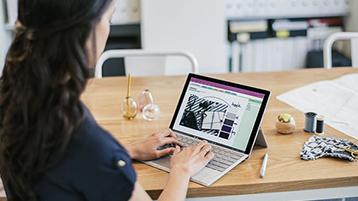Frau an Tisch beim Arbeiten mit einer Signature Type Cover-Tastatur, die mit einem Surface Pro verbunden ist.