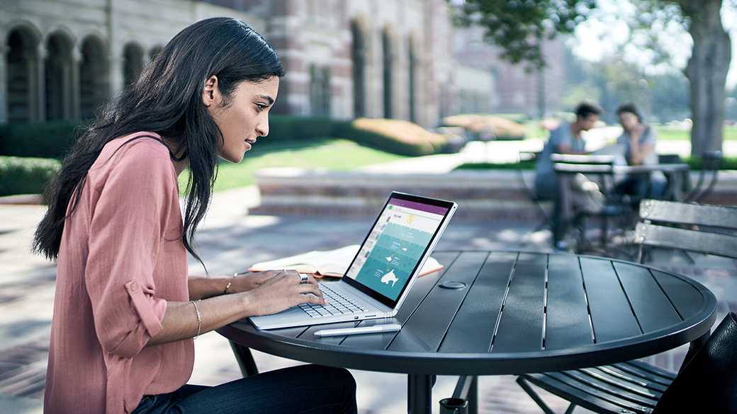 Ein Mann, der an einem Schreibtisch sitzt und auf einem Surface Book mit angeschlossener Tastatur, Maus und Bildschirm mit Surface Dock arbeitet