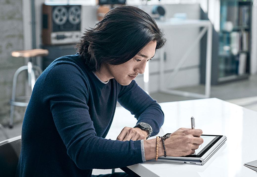 Ein Mann, der am Schreibtisch sitzt und auf seinem Surface Book im Canvas-Modus etwas zeichnet