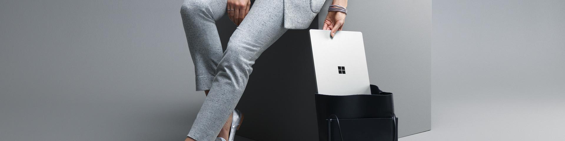 Frau schiebt einen Surface Laptop in ihre Tasche.