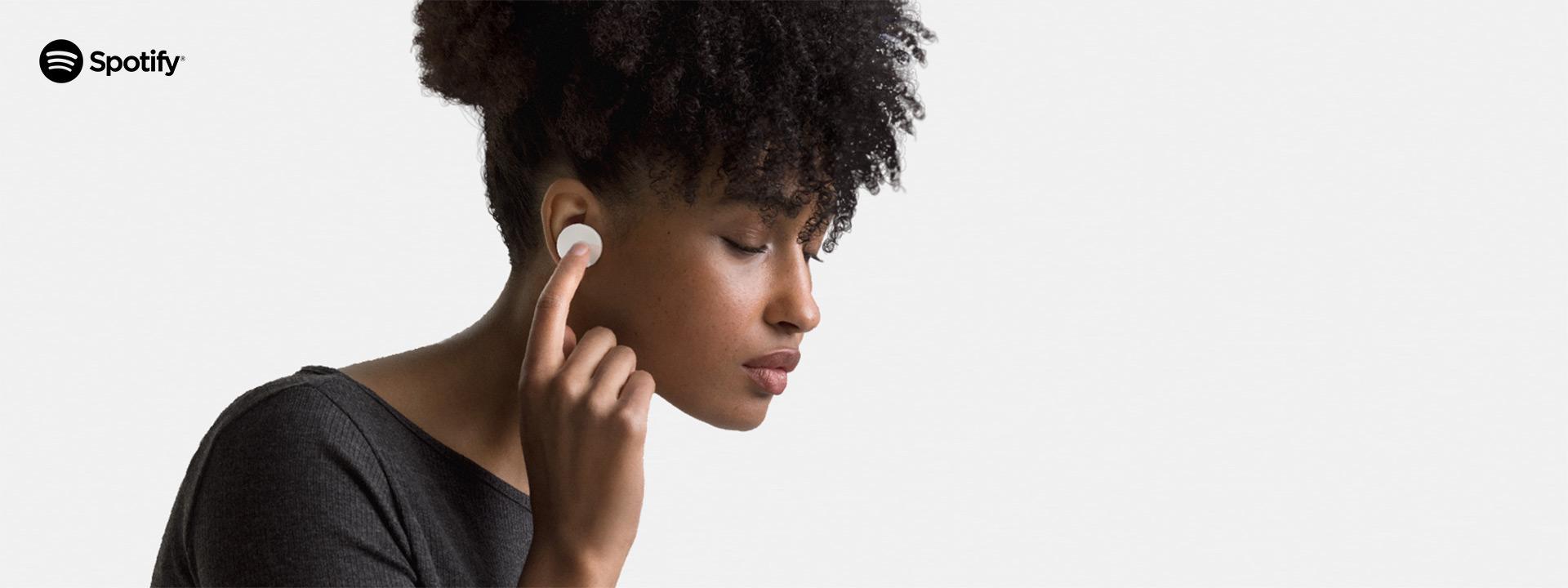 Person tippt, um Spotify mit Surface Earbuds zu steuern.