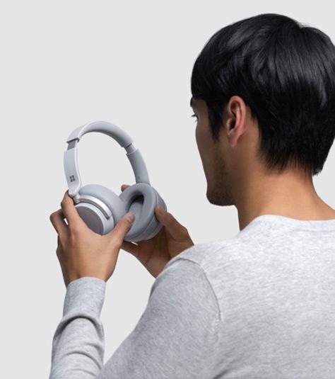 Ein Mann setzt sich Surface Headphones auf den Kopf