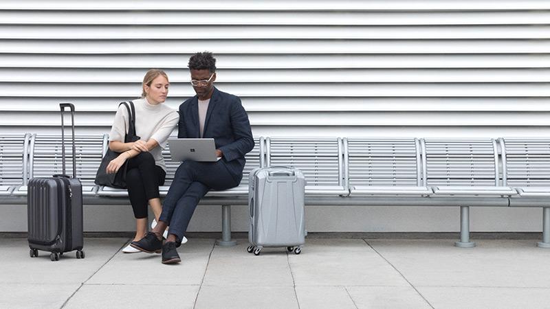 Ein Mann am Flughafen tippt auf einem silberfarbenen Surface Laptop im Laptop-Modus und eine Frau sieht ihm dabei über die Schulter.