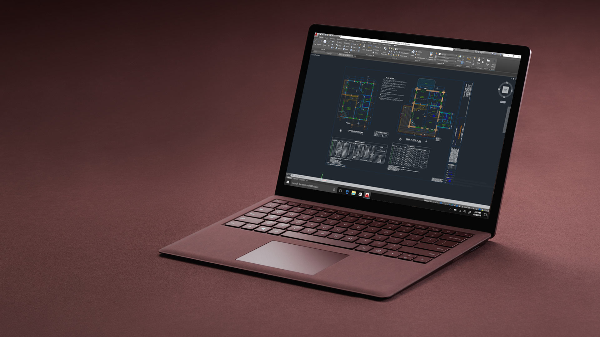 Surface Laptop in Bordeaux Rot mit AutoCAD-Bildschirm.