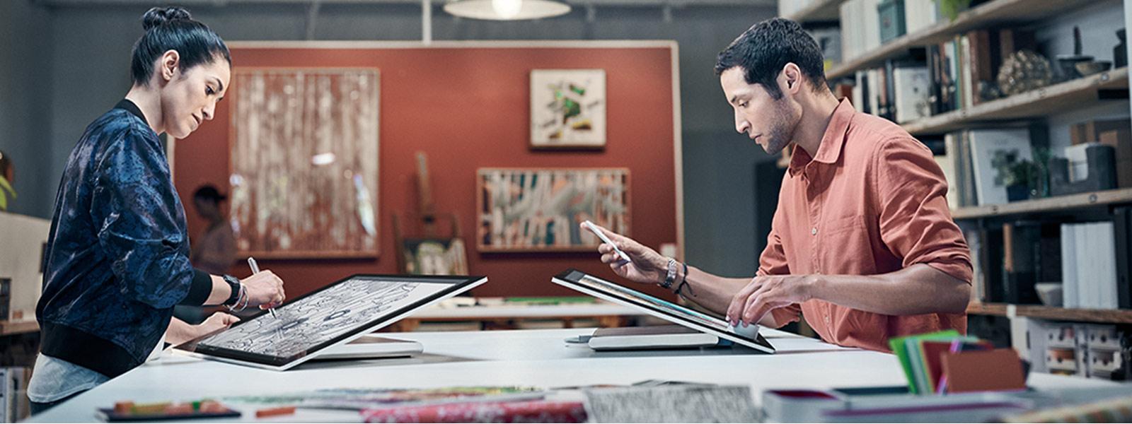 Ein Mann und eine Frau sitzen sich am Arbeitsplatz gegenüber, beide arbeiten mit Surface Studio im Studiomodus