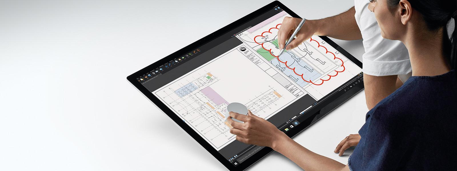 Zwei Personen arbeiten mit Surface Studio und verwenden dabei das Surface Dial und den Surface-Stift