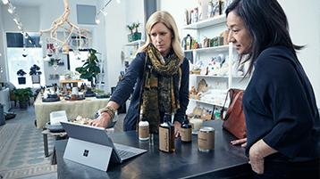 Eine Frau zeigt auf den Bildschirm eines Surface Pro 4 in einem Geschäft, während eine andere Frau genau zusieht