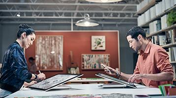 Ein Mann und eine Frau sitzen sich am Arbeitsplatz gegenüber, beide arbeiten mit Surface Studio im Studio-Modus
