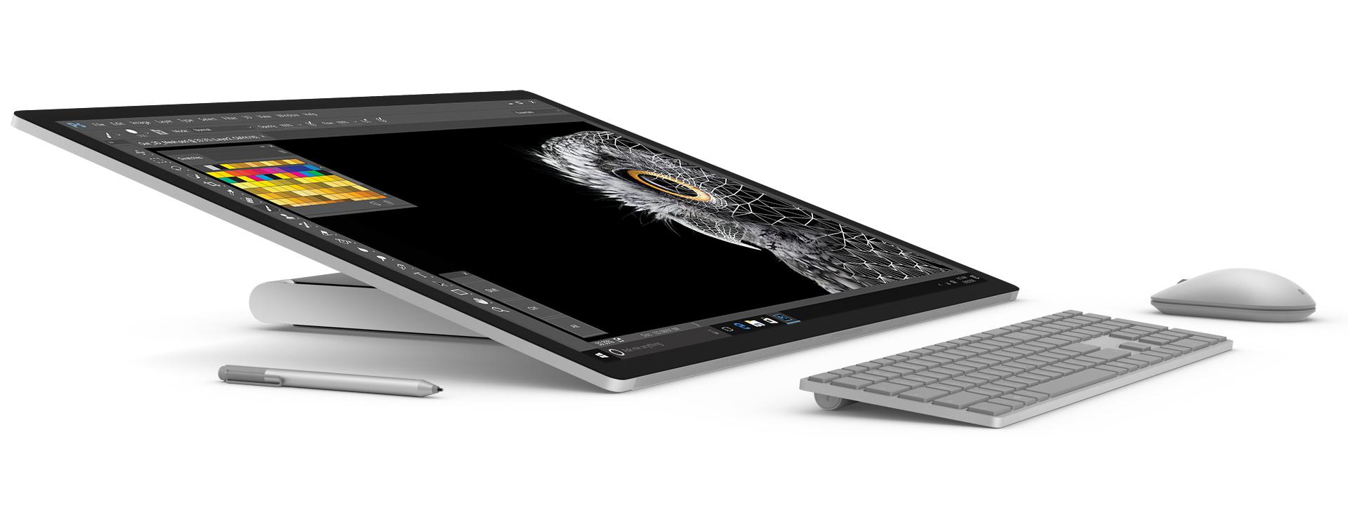 Surface Studio flach im Studiomodus nach rechts gerichtet, Surface-Stift, -Tastatur und -Maus davor
