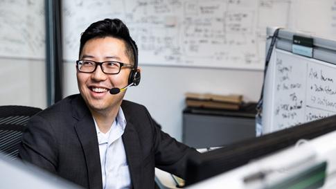 Mann trägt ein Headset und sitzt am Arbeitsplatz