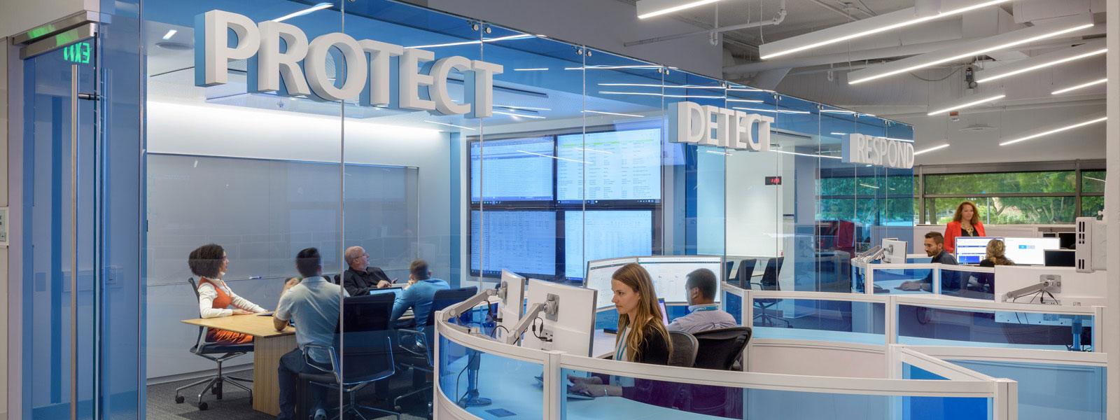 Benutzer arbeiten in Konferenzräumen und an Schreibtischen im Sicherheitserkennungscenter
