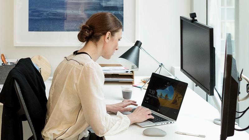 Frau meldet sich mit Windows Hello bei einem Laptop an