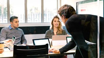 Personen mit Laptops sitzen um einen Konferenztisch herum
