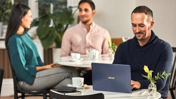 Mann bedient Laptop an einem Tisch in einem Café