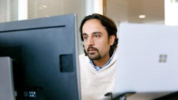 Mann sitzt am Schreibtisch und blickt auf den Bildschirm