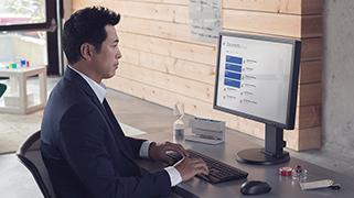 Geschäftsmann, der an einem Computer sitzt und tippt