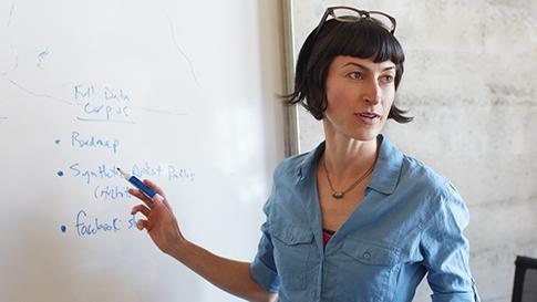 Frau schreibt auf Whiteboard