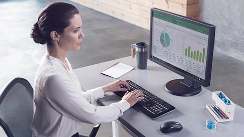 Frau schaut sich Diagramme und Grafiken auf einem Computerbildschirm an