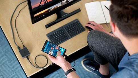Mann, der mit einem Smartphone arbeitet, das über ein Kabel mit dem Bildschirm verbunden ist