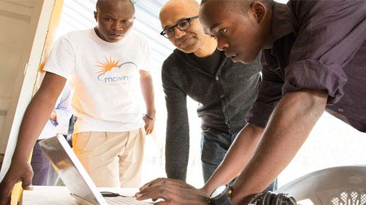 Satya Nadella und zwei junge Männer betrachten einen Laptop