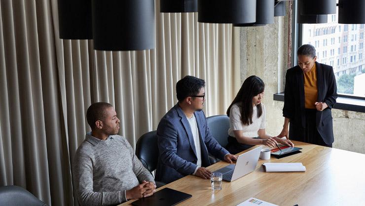 Teilnehmer einer Besprechung sitzen mit ihren Surface-Geräten an einem Konferenztisch