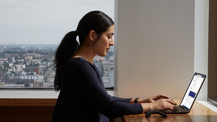 Eine Person tippt auf einem Surface Laptop