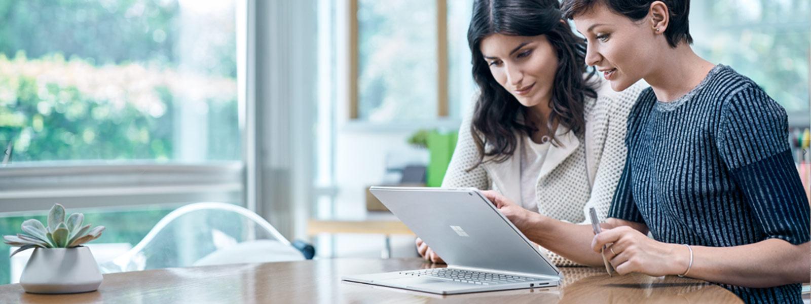 Frau zeichnet mit Surface Pen auf Surface Studio-Bildschirm und zoomt mit der anderen Hand