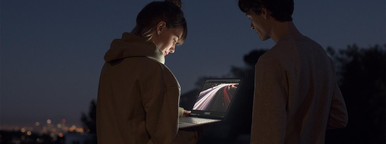 Ein Mann und eine Frau blicken auf ein PixelSense™-Display von Surface.