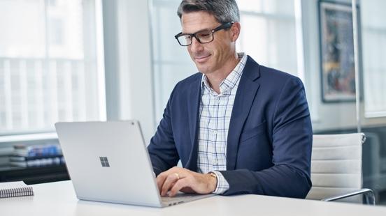 Επιχειρηματίας μπροστά από ένα Surface, όπου παρακολουθεί ένα webinar για το PSD2
