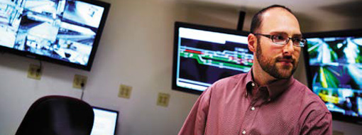 Ένας άνδρας σε ένα γραφείο με πολλές μεγάλες οθόνες πίσω του