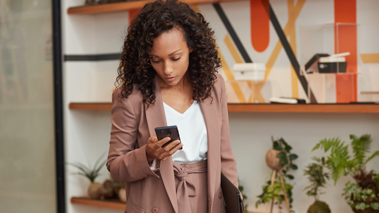 A woman stands in her home office holding a folder and looking at her phone