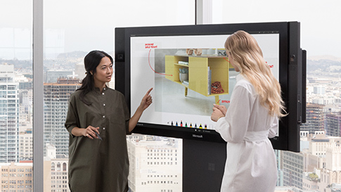 Two women use touchscreen on a Surface Hub, using the Microsoft Whiteboard app to draw on a design.
