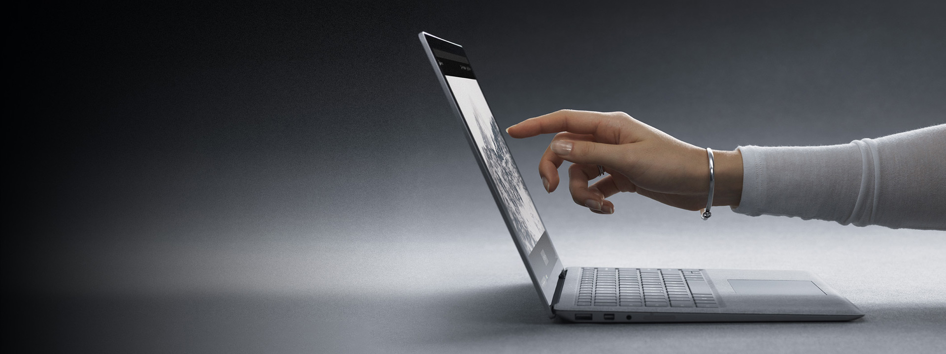 A girl touches the screen on a Surface Laptop 2