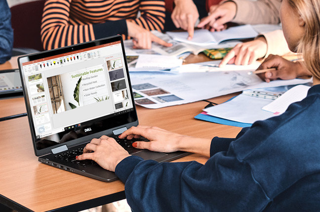 A woman using her Windows 10 computer to design a PowerPoint presentation
