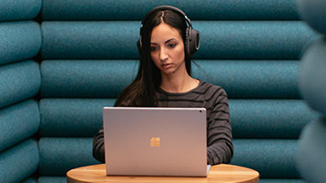 A woman sits quietly in solitude while wearing headphones as she works on her Windows10 computer