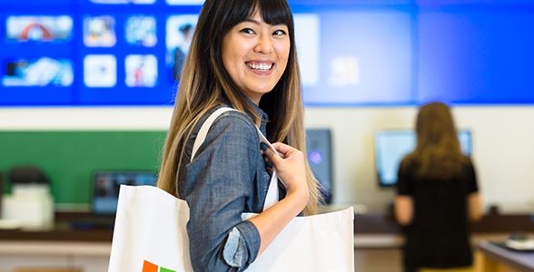 Female smiling and shopping at Microsoft store.