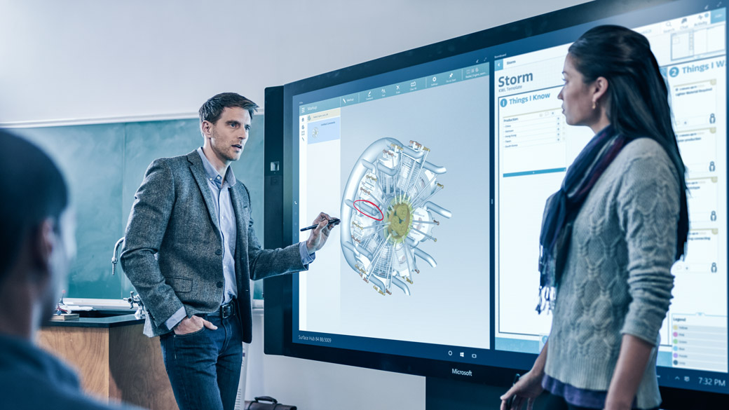 Teacher uses Surface Hub to give presentation in classroom.