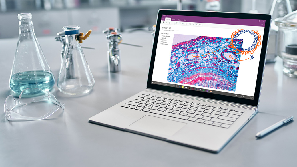 Surface Book on a table with a pen next to it.
