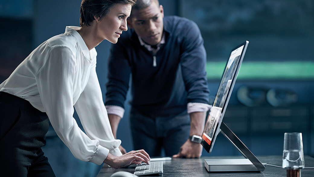 Woman types on Surface Keyboard In front of Surface Studio while a man stands by looking at the screen.