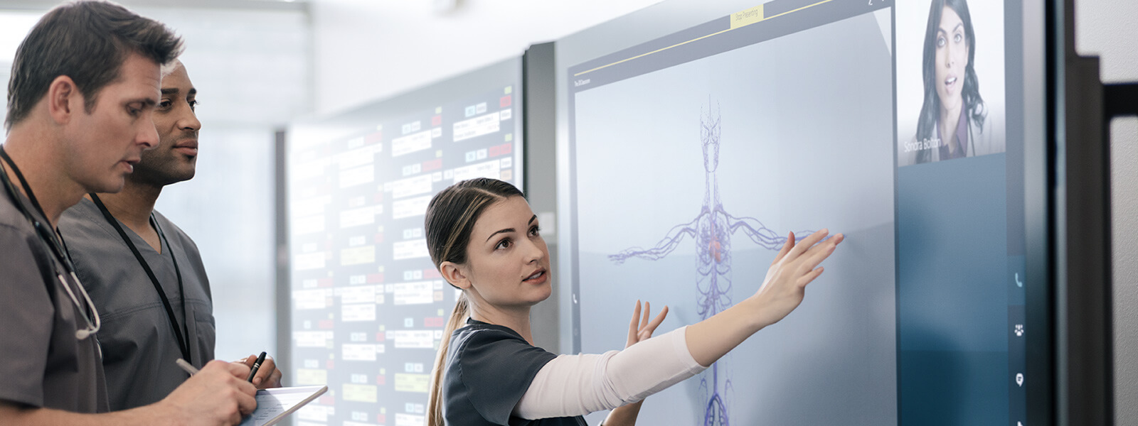 Doctor uses touchscreen on Surface Hub while two other doctors take notes in background.