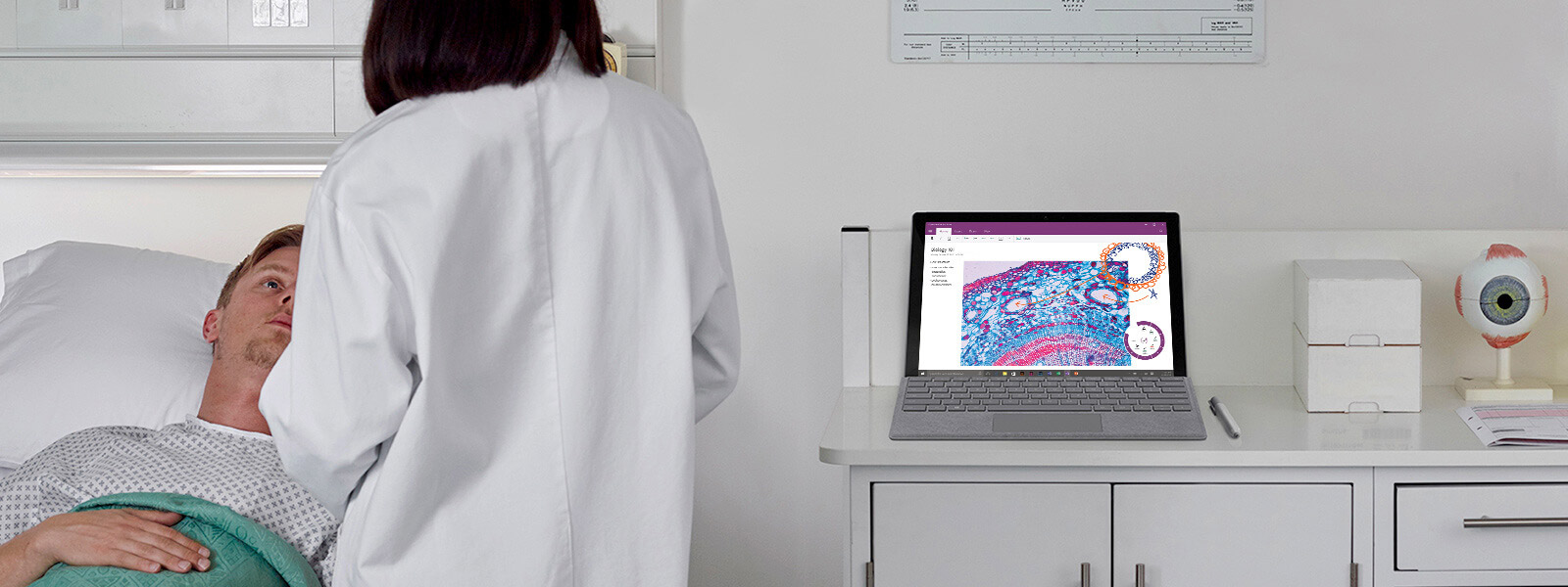 Doctor talks to patient at bedside, and Surface Book sits on table in background.