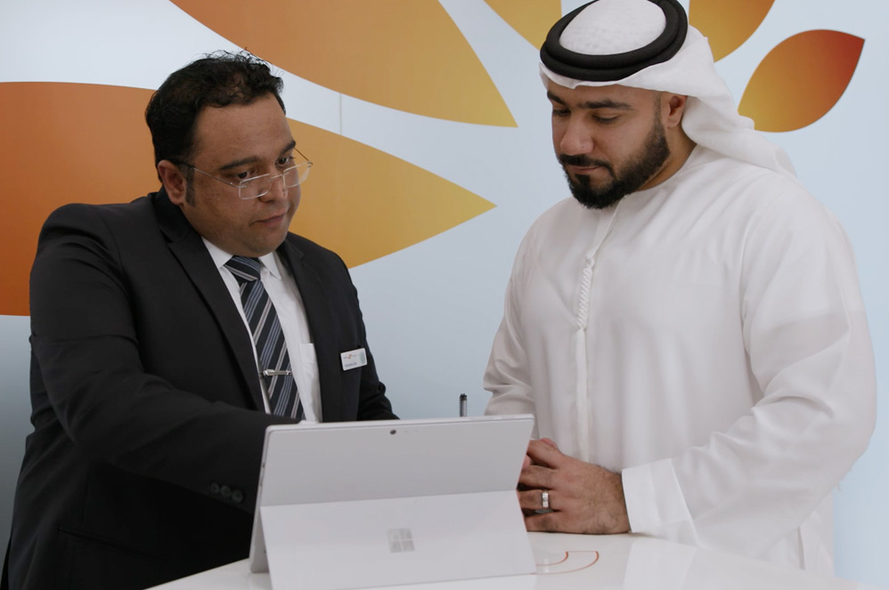 Two Mashreq employees work opposite each other on their Surface Pro devices