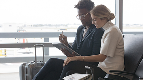 Man and woman sit at an airport, and look at the screen of a Surface Pro in tablet mode.